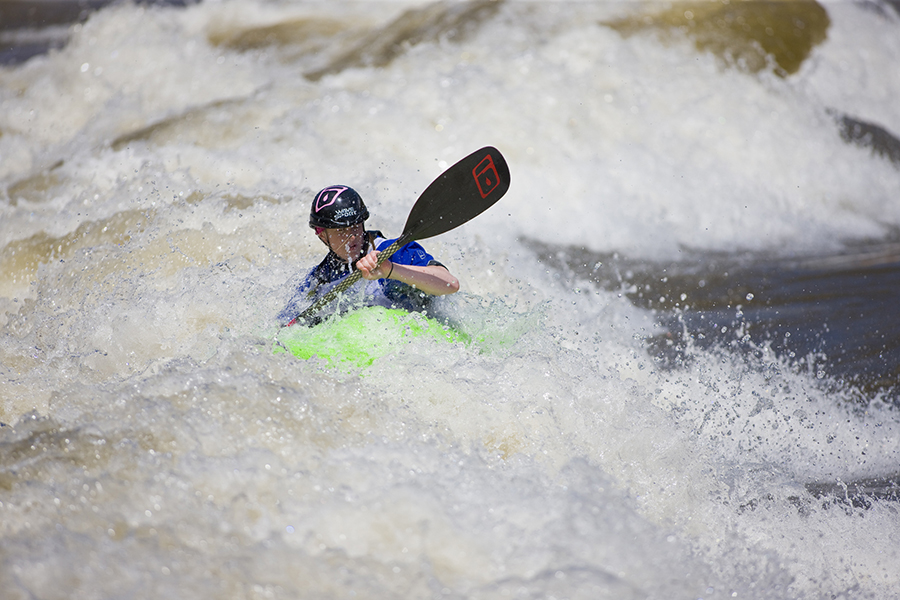 Riding a bright green kayak, a young man navigates frothing rapids in Glenwood Whitewater Park & Activity Area.