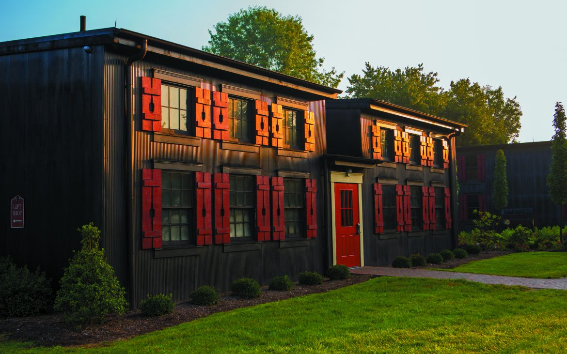 Brown building with red accents with manicured green lawn