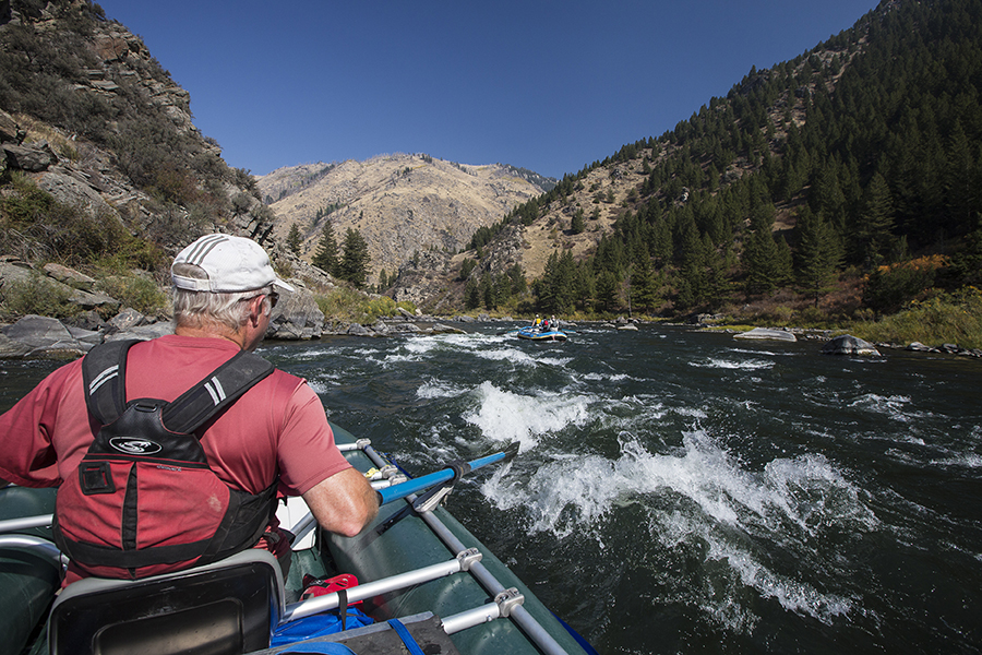 Using oars, a man guides his boat through whitewater in Montana with mountains in the background.