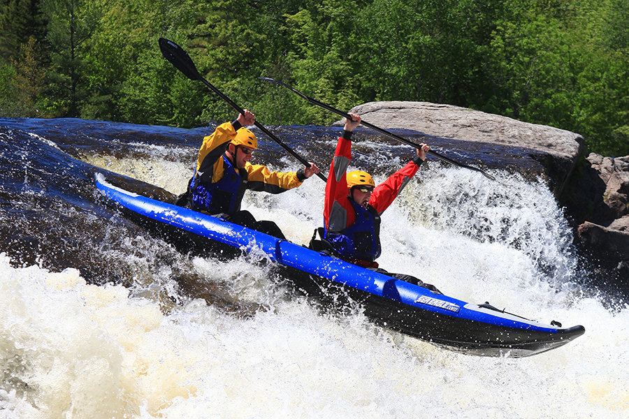 Riders of a blue kayak raise their oars in jubilation as their vessel plummets down gushing waterfalls on the Penobscot River.