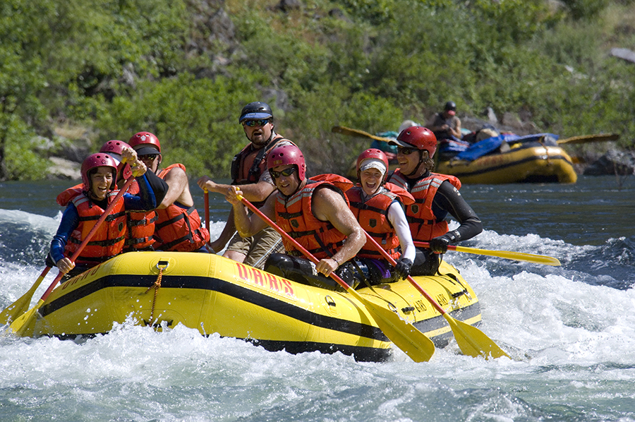 A group of rafters paddle through whitewater on the Merced River in California.