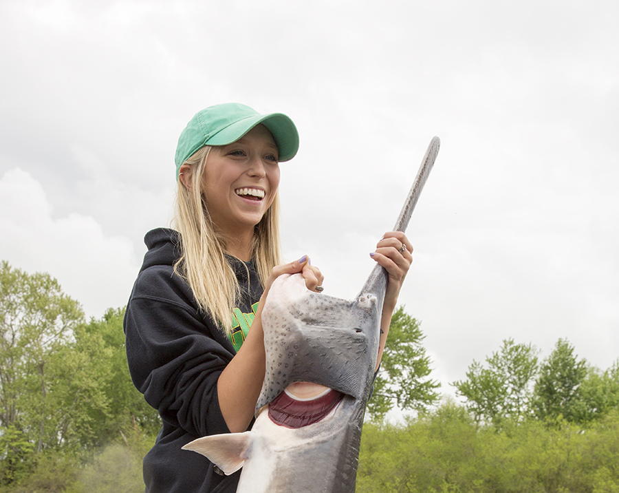 An angler proudly shows off the paddlefish that she caught.