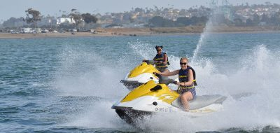 Couple riding yellow and white jet skis on bay