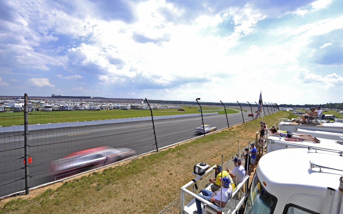 Cars racing around racetrack with fans looking from RVs