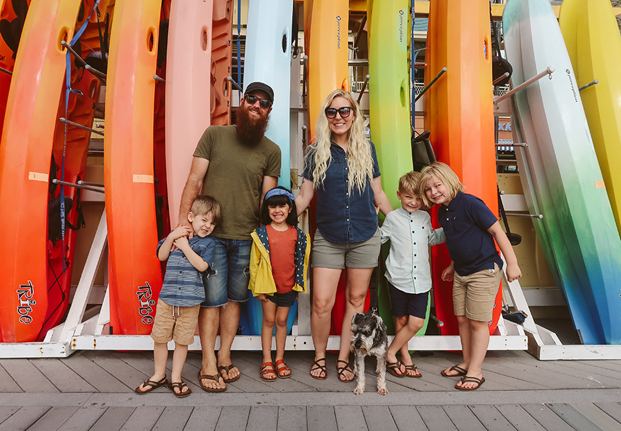 Family of six posing in front of surfboards