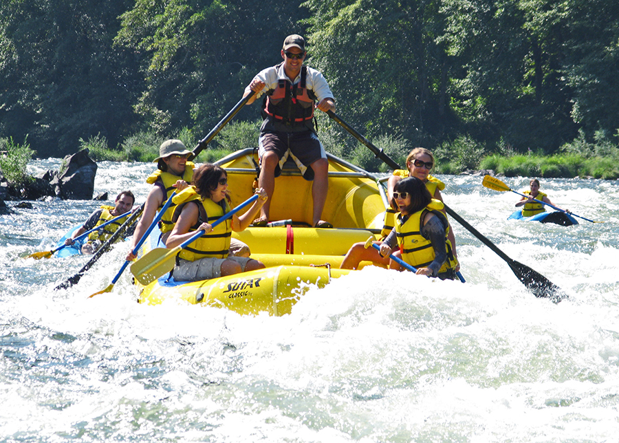 A yellow raft laden with fun seekers paddles on a rough part of the Rogue River.