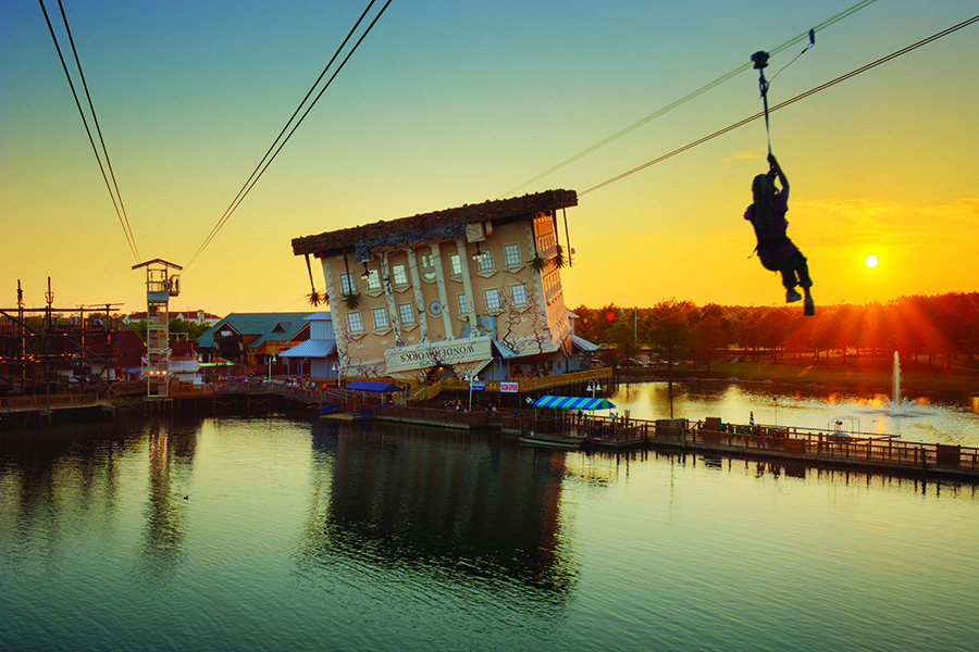 A zipline zooms across a lake with the Wonder Works building in the background.