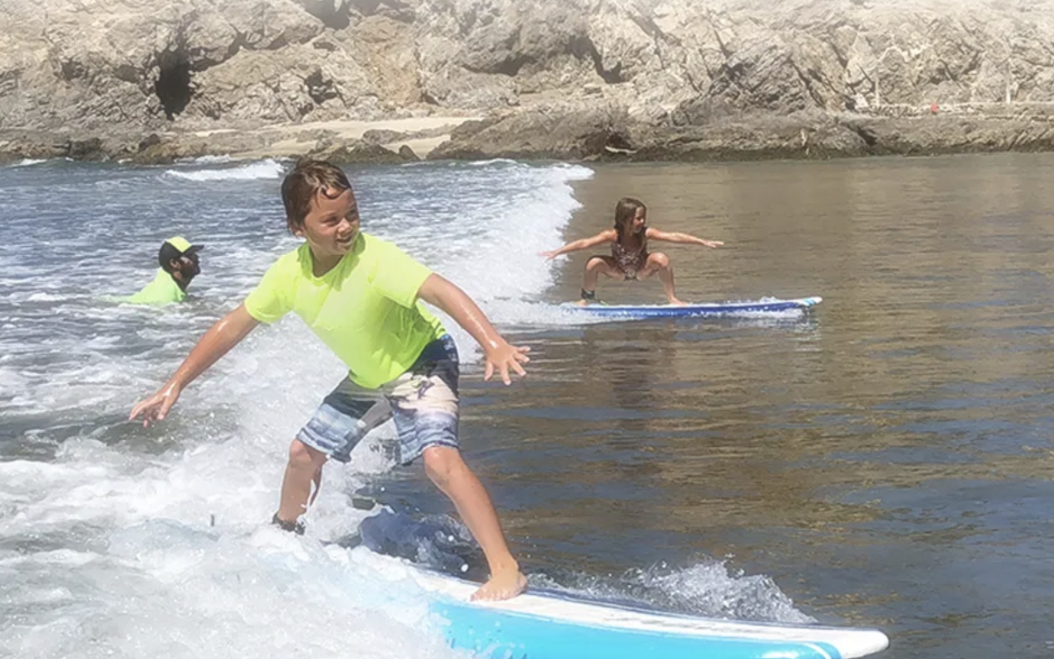Young boy surfing with green shirt and young girl surfing next to him