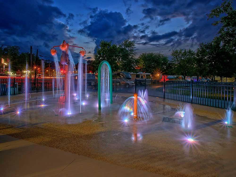 Colorfully lit children's splash pad at night