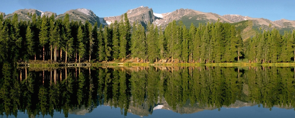 A mountain lake in the Colorado Rockies reflects the trees that line the shore.