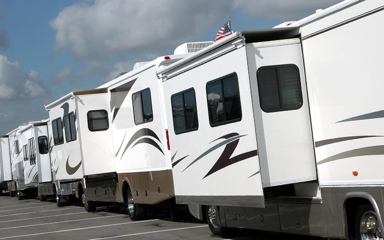 Motorhomes parked end-to-end on asphault.