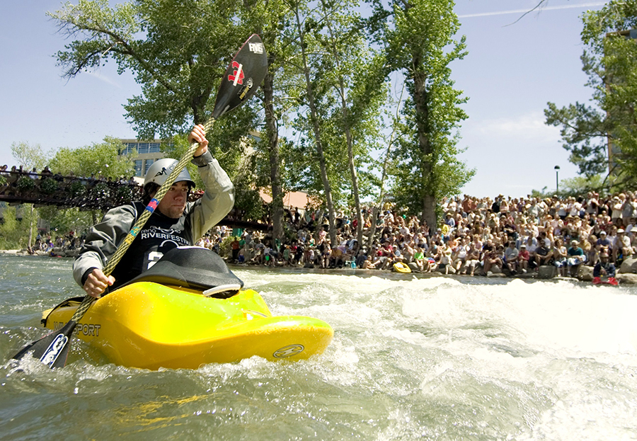 A kayaker propels his bright yellow kayak in front of a crowd through the whitewater in the Truckee Whitewater Park in Reno.