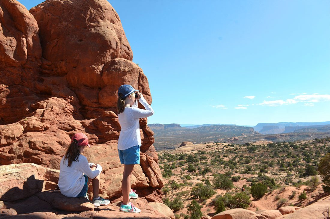 Two children look out over the rocky landscape of Canyonlands National Park