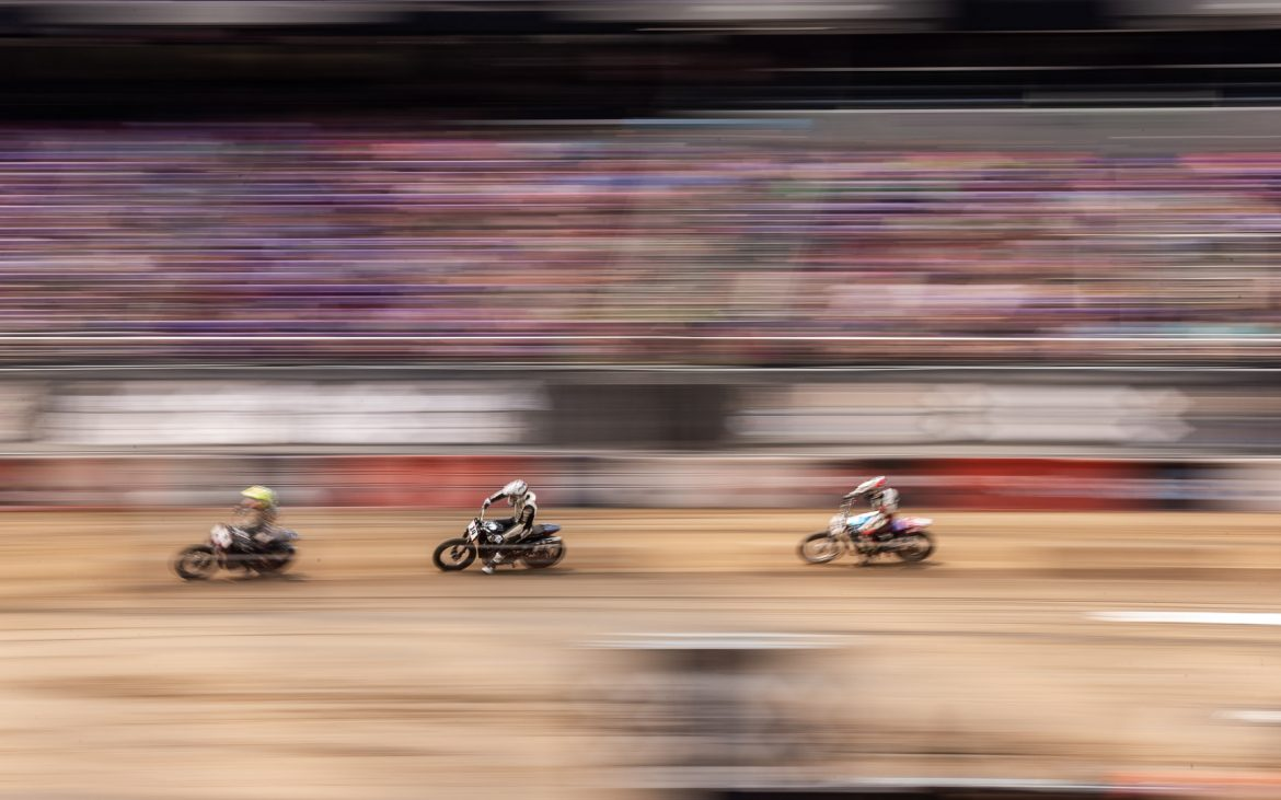 Three blurry motorcycle riders on dirt track racing