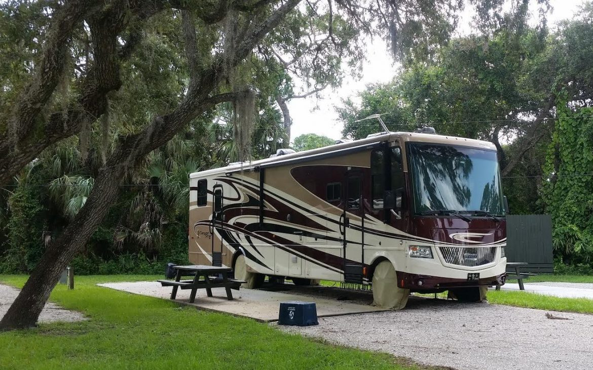 Large brown, tan and taupe RV alongside firepit and picnic table
