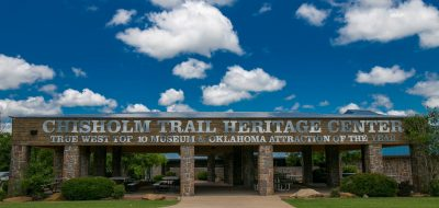 Wooden Chisholm Trail entrance sign against blue sky