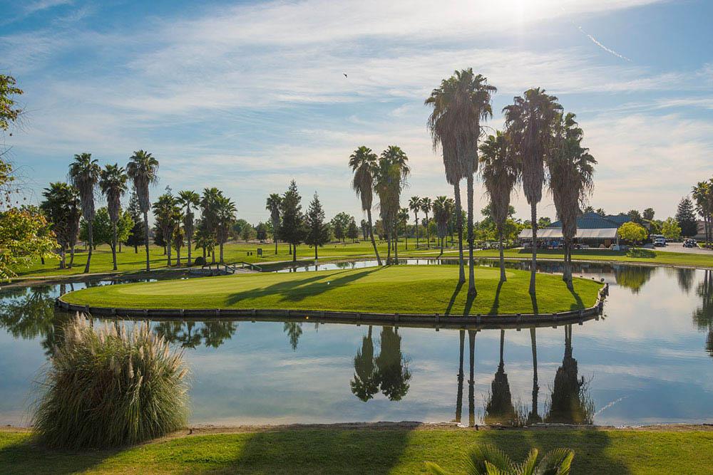 Glassy lake alongside green golf course