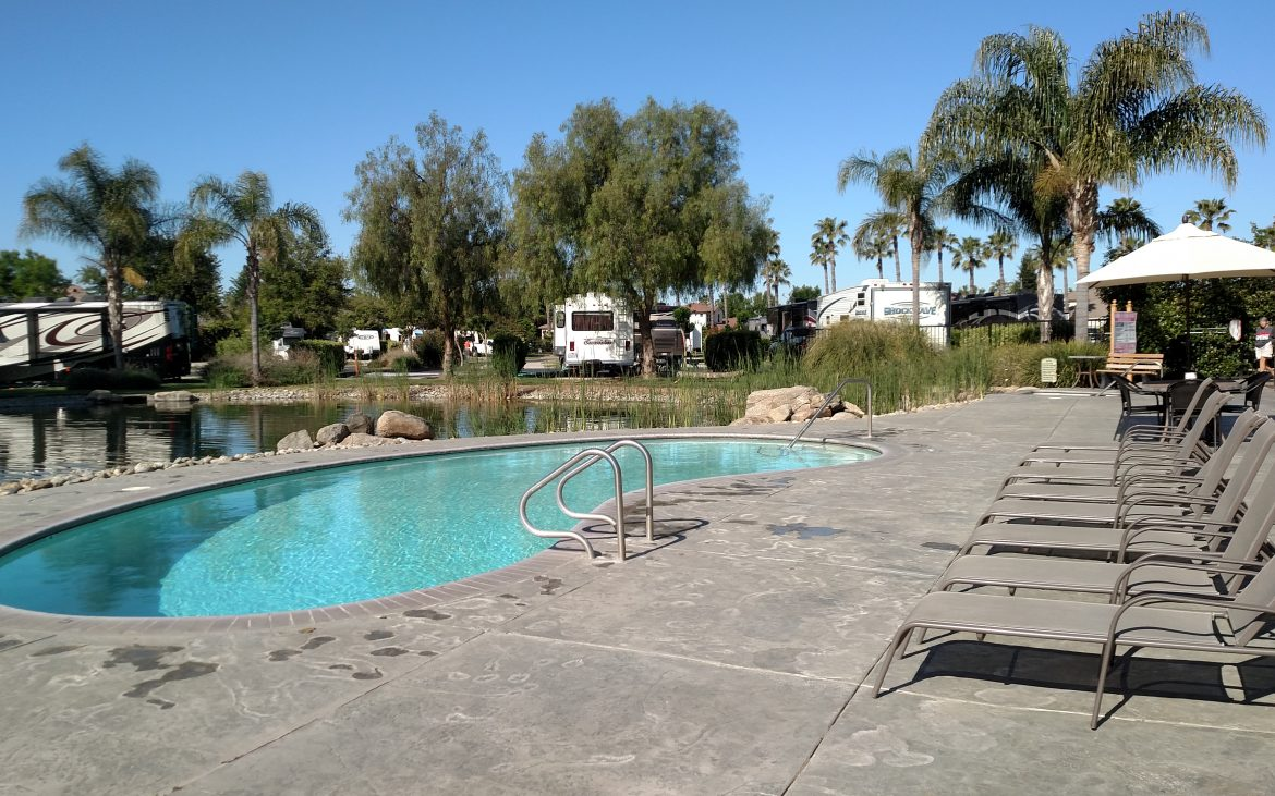 Clean community pool with RV and Trailers in the background