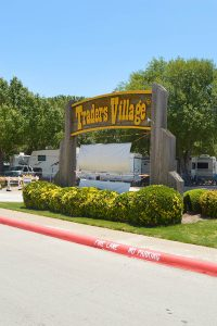 Brown and yellow wooden Traders Village entrance sign