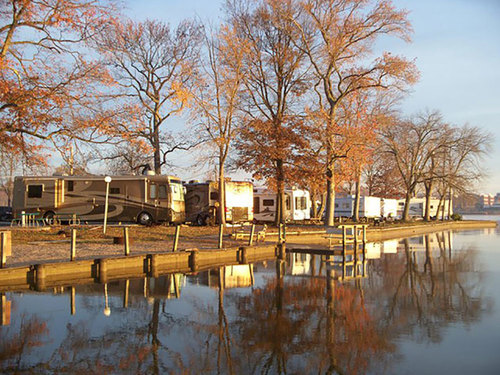 Large trailers parked along waterway with trees in the fall