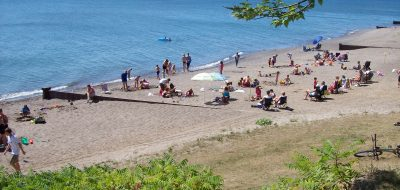 Dozens of campers relaxing and playing on the sandy beach
