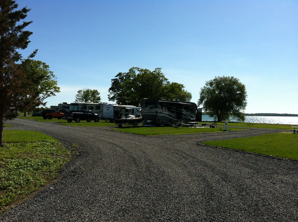 Many RVs parked along gravel and dirt road