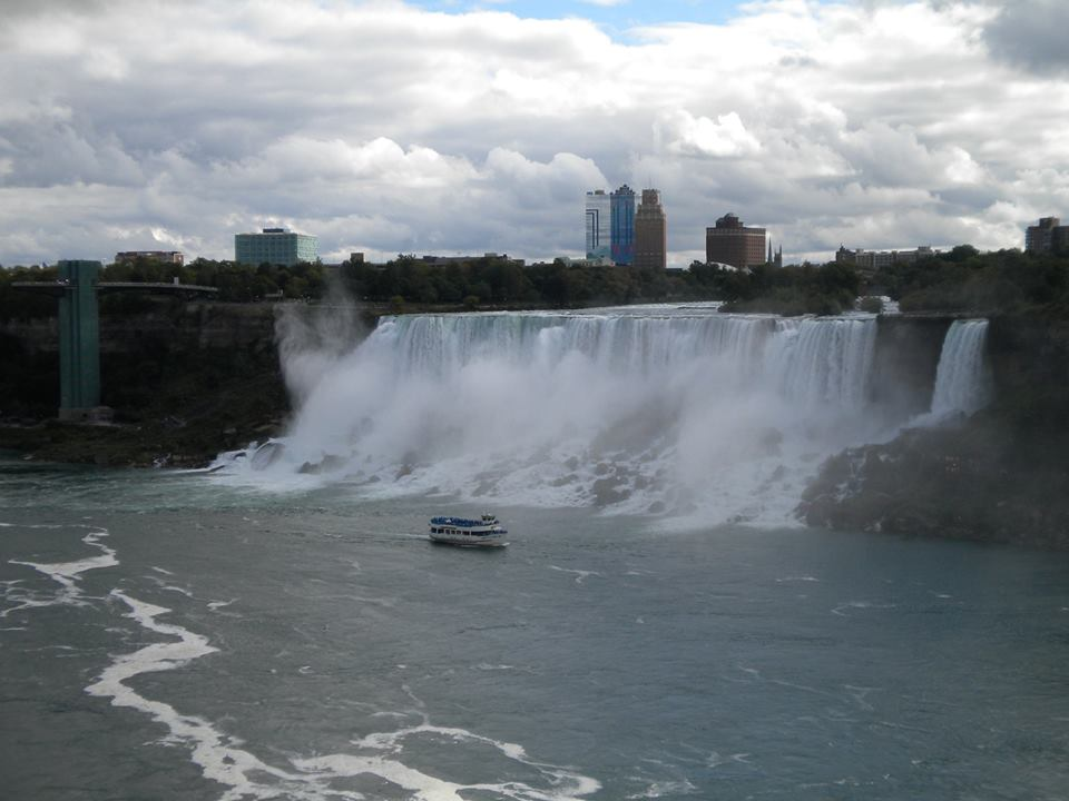 Massive waterfall pouring over behind floating ferry.