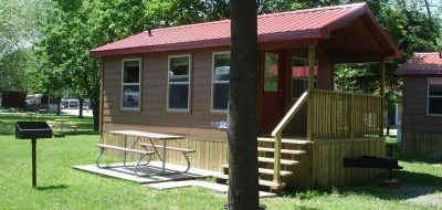 Cabin with red roof alongside picnic table