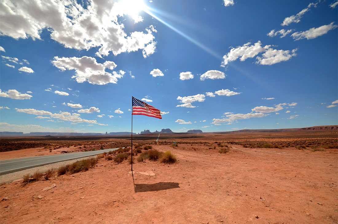 A flag waves in the desert while Monument Valley's buttes and mesas form a dramatic backdrop in the distance.