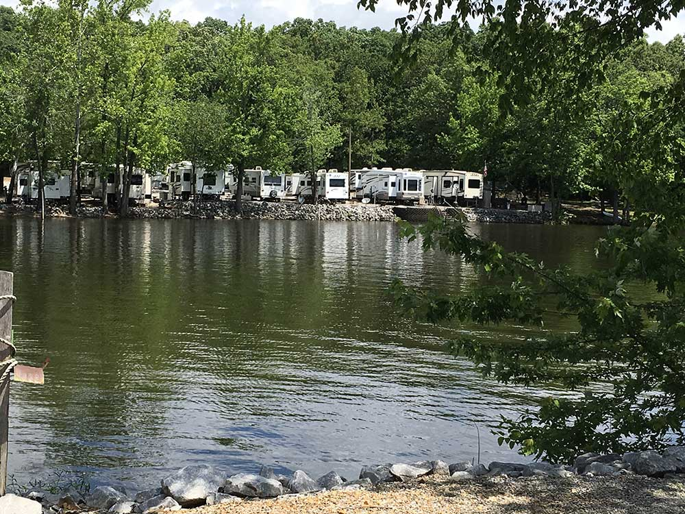 Many white RVs parked along the water