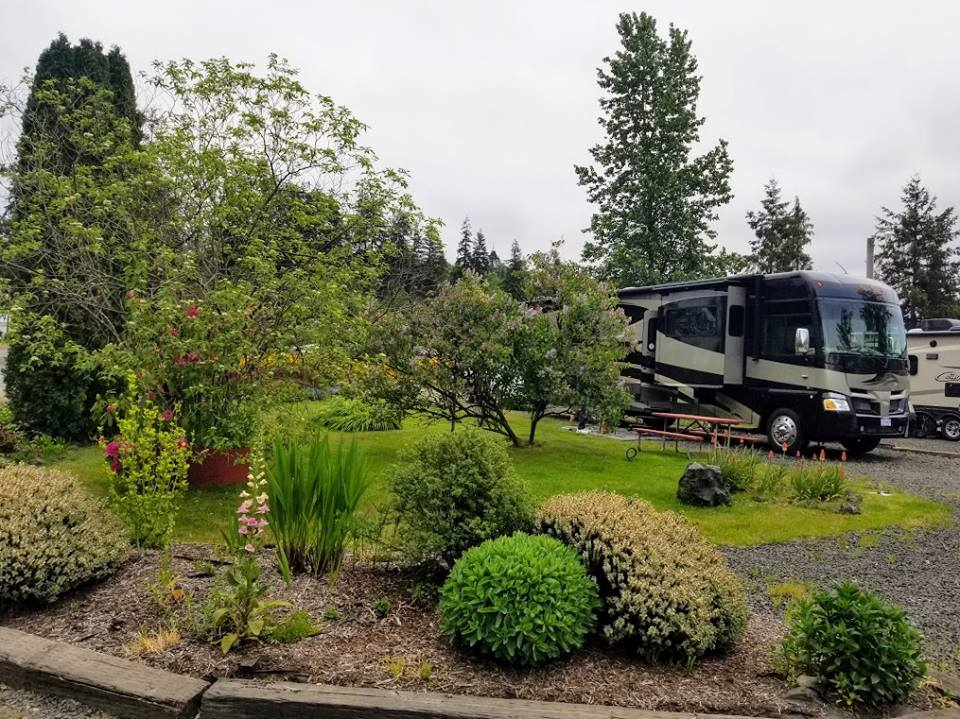 Large RV in spot alongside beautiful landscaping