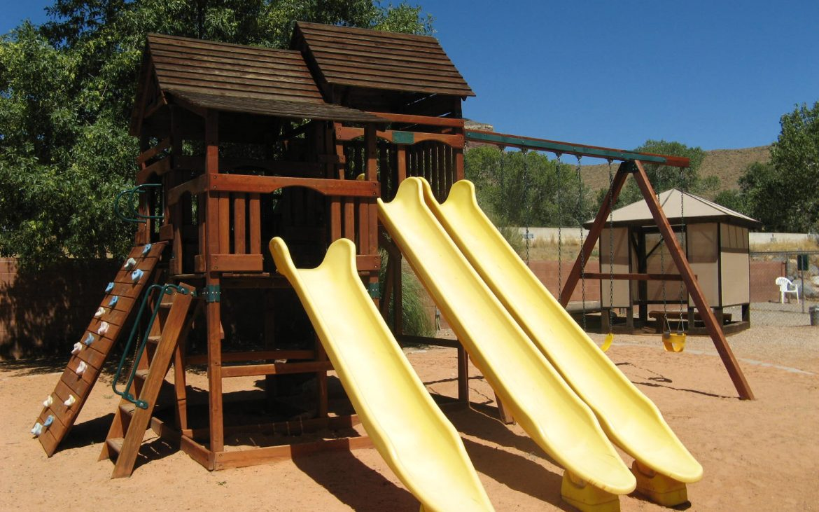 Wooden outside playhouse with three yellow slides on sandy area