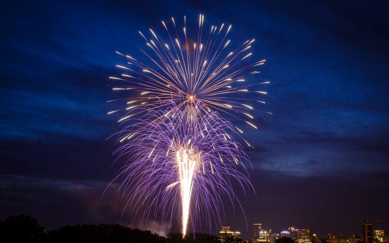 Fireworks over river with dark lavender blue sky