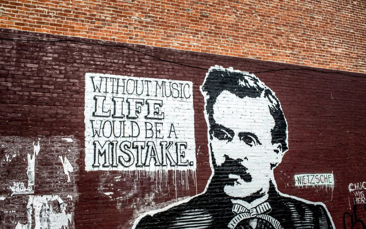 Brick wall with spray painted man's face and music quote