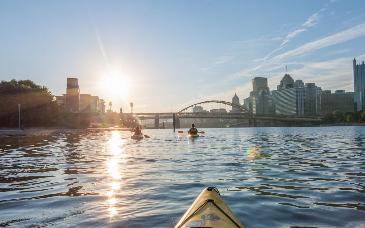 Sunrise over Pittsburgh river with kayakers heading toward bridge