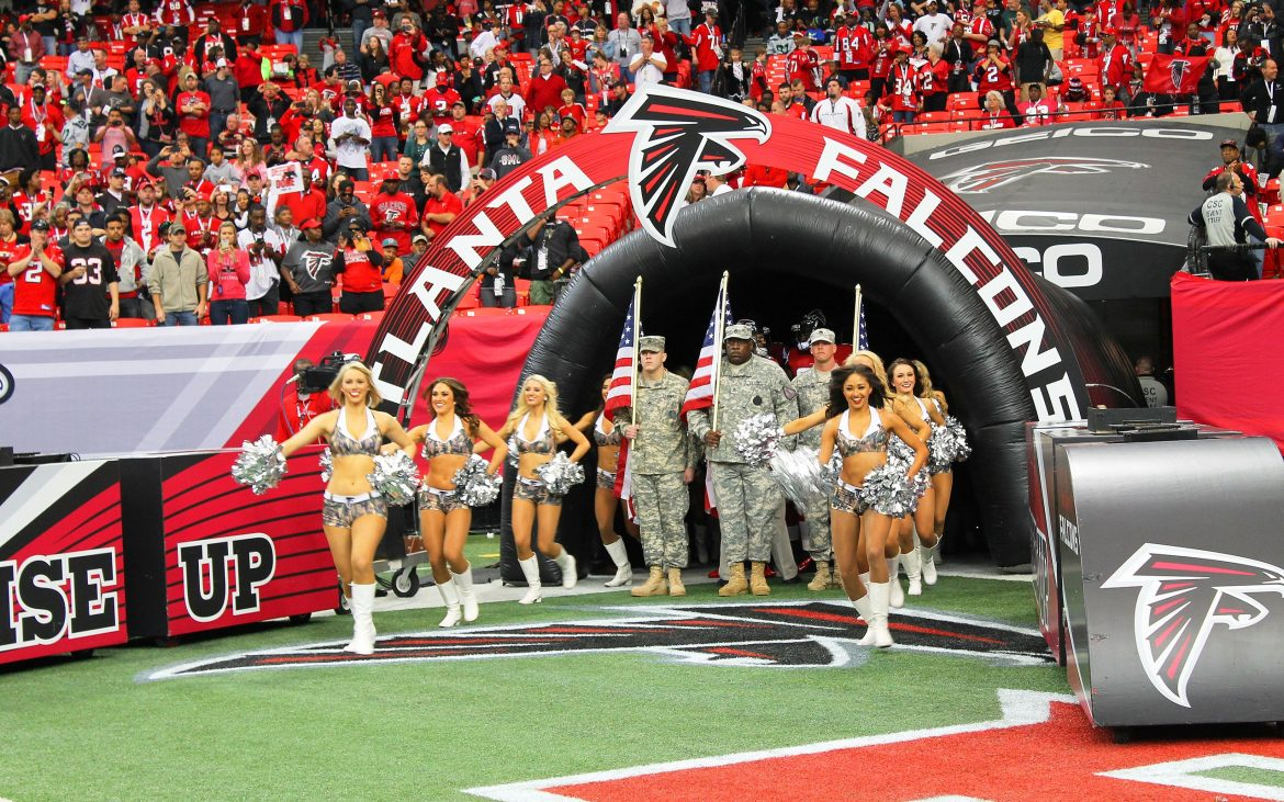 Military troops holding American flags at NFL tunnel with cheerleaders