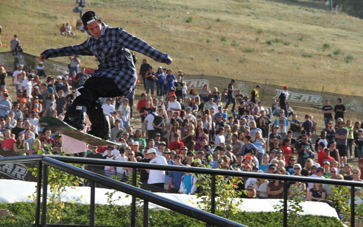 Young male snowboarder doing a trick on railing with crowd watching