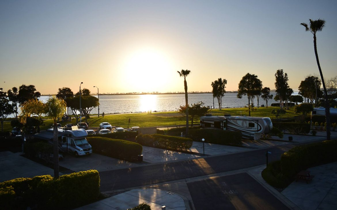 Sun setting over ocean and RV park with palm trees