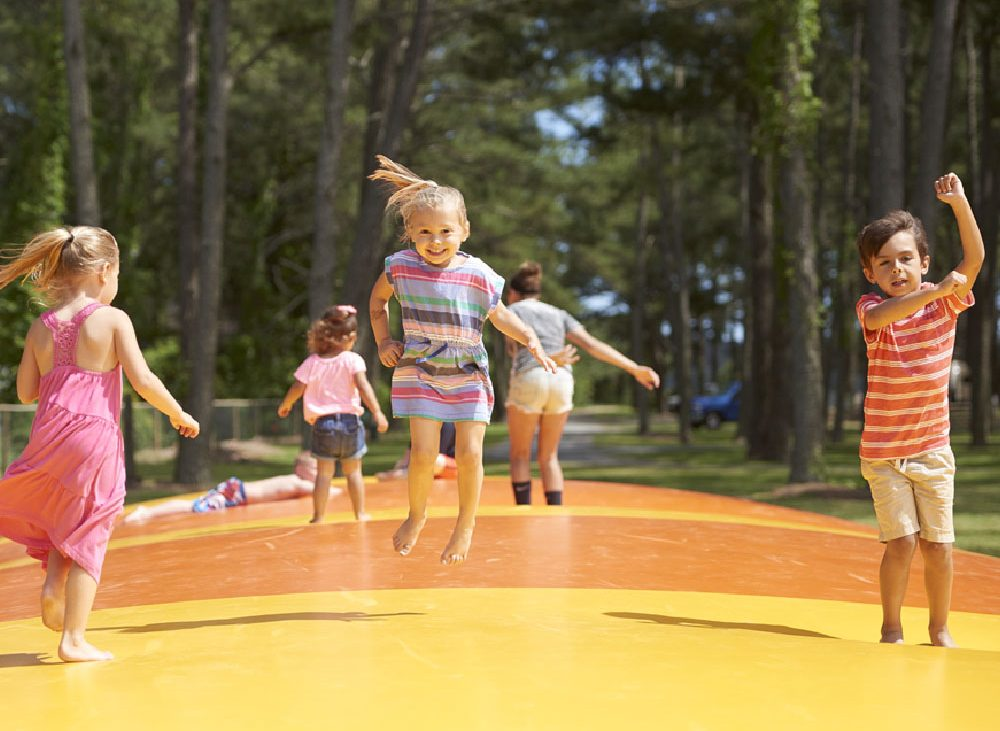 Group of children jumping on orange and yellow pad