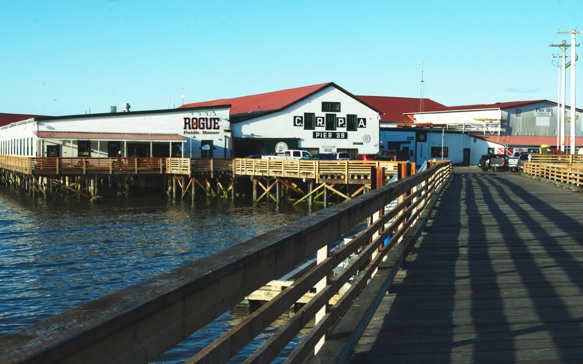 Brewpub white and red building on pier on ocean