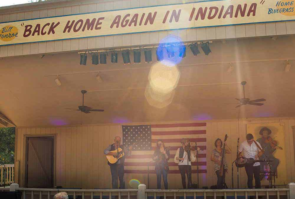 Musicians with acoustic instruments on a stage with an American flag in the background.