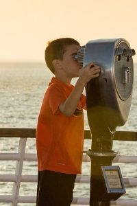 Boy in orange shirt staring out through a viewfinder