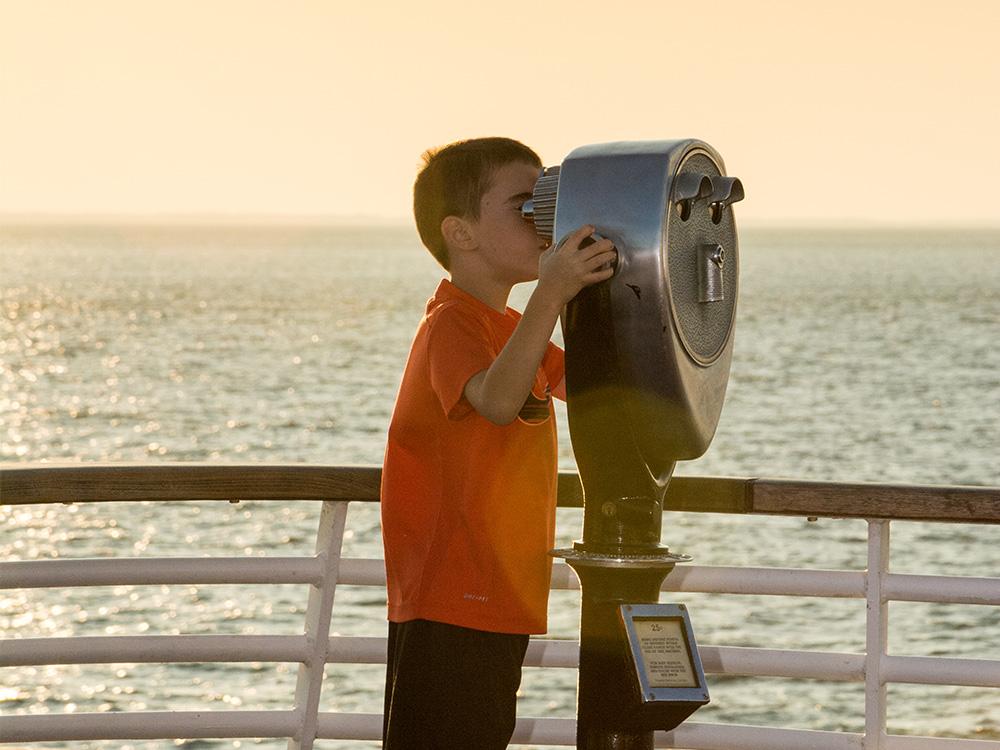 Boy in orange shirt staring out through a viewfinder
