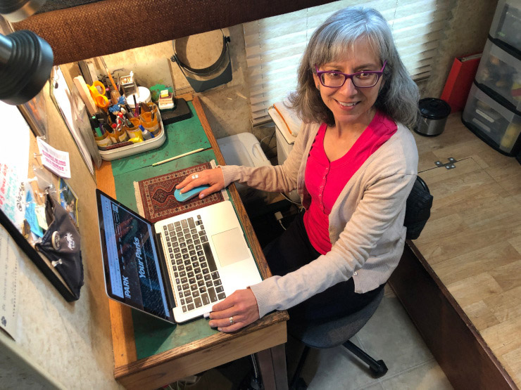 Author Rene Agredano seated at her computer desk in a renovated space in the RV.