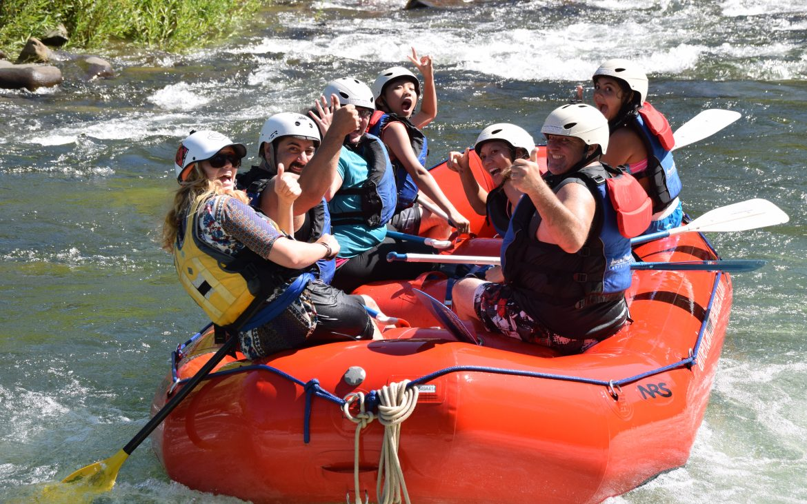 Group of people smiling at camera on raft going down American River