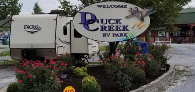 Front entrance sign with trailer parked alongside