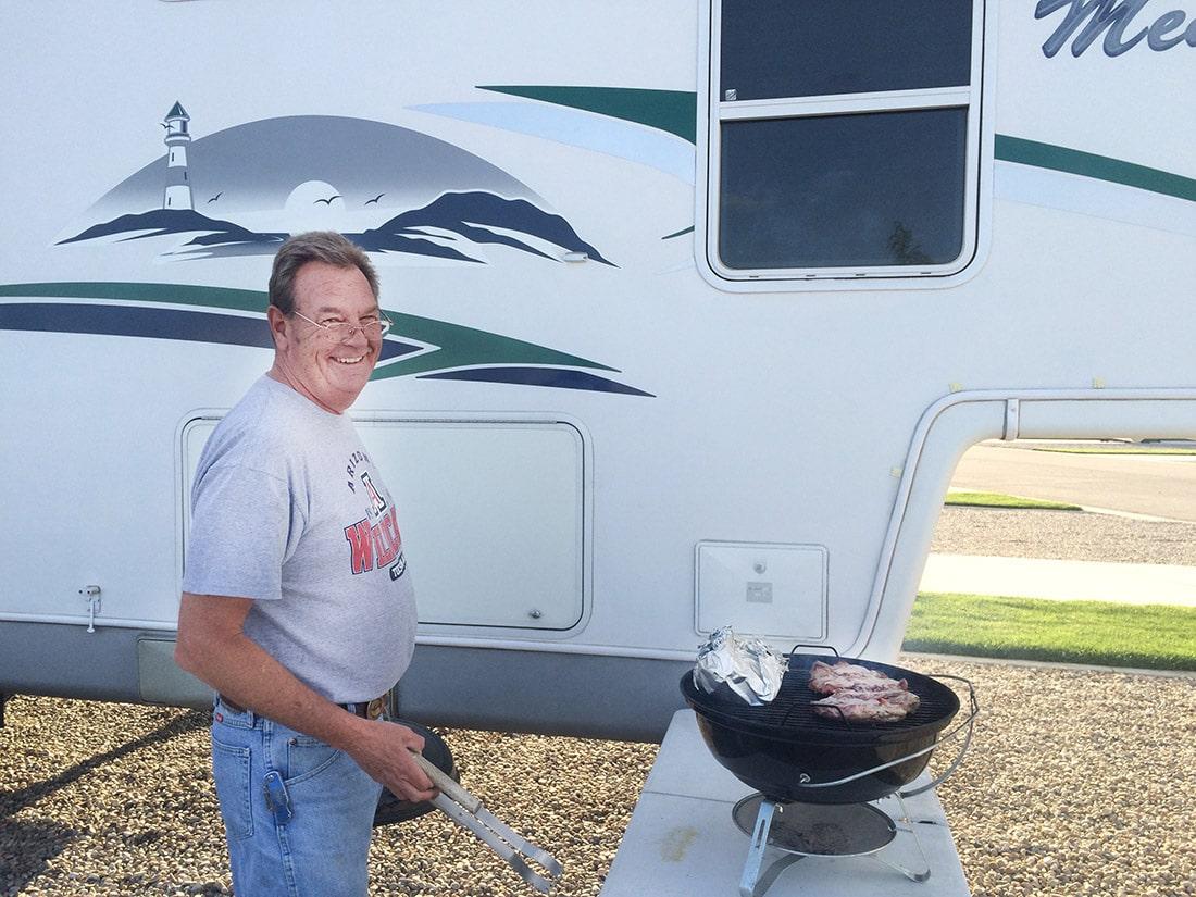 Grilling up a pair of juicy steaks outside of the fifth-wheel trailer.