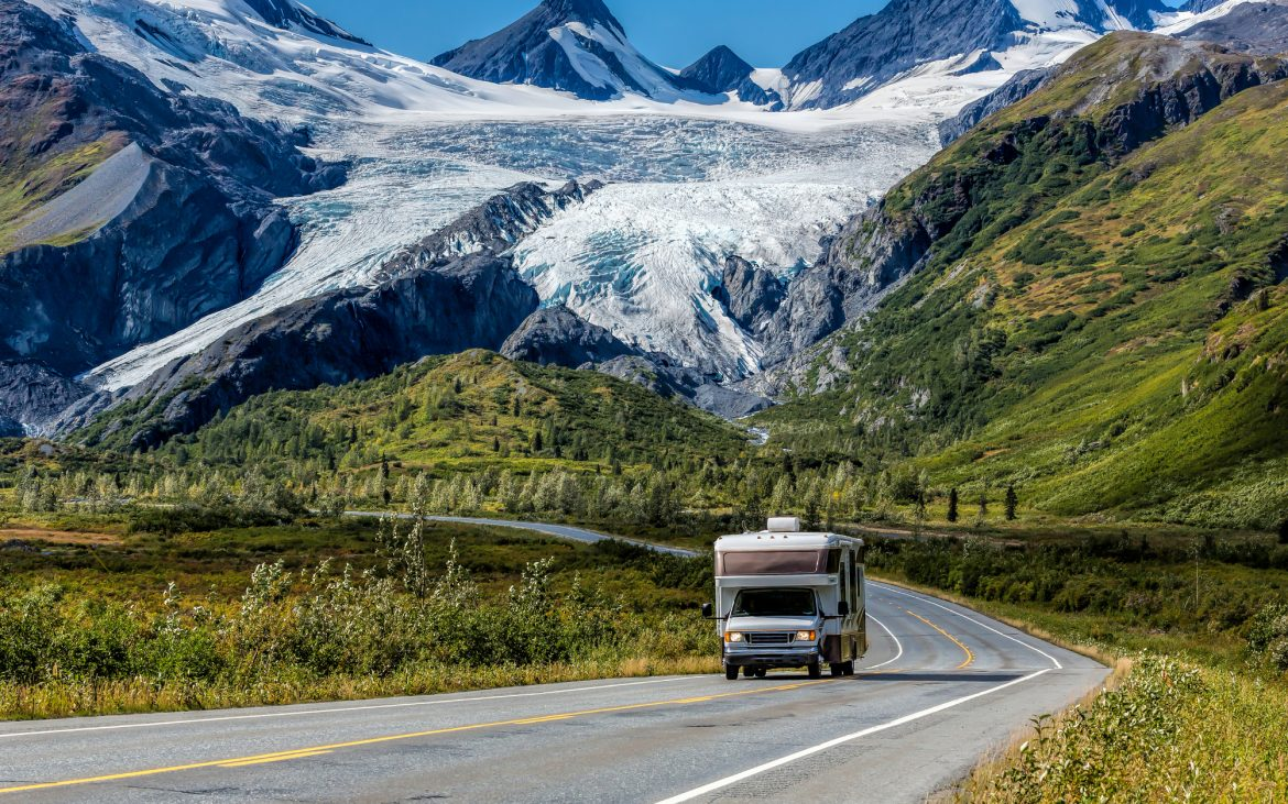 An RV travels along the Richardson Highway in Alaska. In the background is Worthington Glacier.