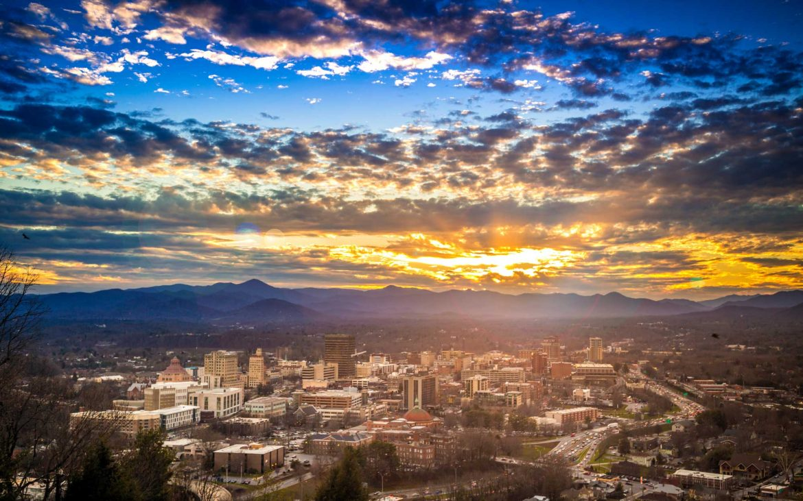 Epic Sunset over Downtown Asheville North Carolina NC cityscape with blue ridge mountain range and Mt. Pisgah featured in the background.