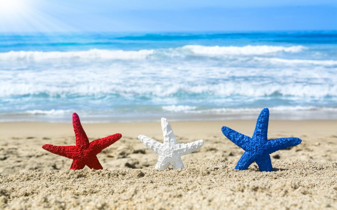 Conceptual summer holiday image of three red, white and blue starfish on the beach overlooking a turquoise ocean while celebrating the July fourth holiday.